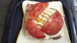 食パンにチーズ、ベーコン、卵、トマトをのせた写真