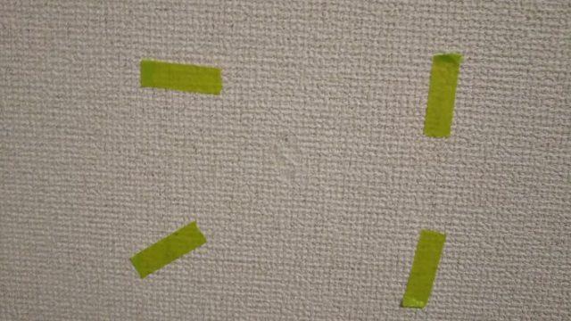 貼った壁紙が浮いてこないようにマスキングテープで固定する写真