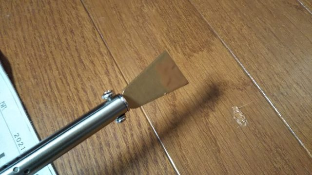 コテ先で溶けたカラースティックを、床のキズ後に流し込む写真