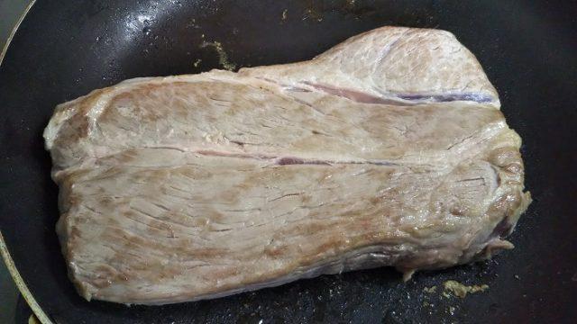 豚肩ロースかたまり肉を、焼き色がつくまで焼く写真