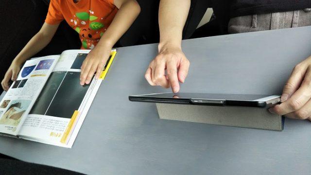 車内テーブルでタブレット端末を操作している写真