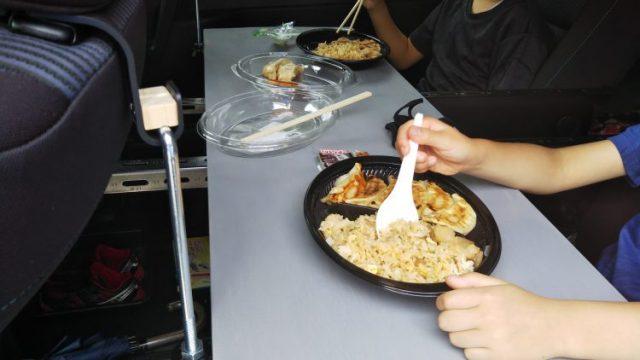 車内テーブルで子供たちが食事をしている写真